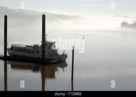 Porto, Portugal - February 3, 2016: Beautiful Douro river in the morning mist, north of Portugal, seeing a small passenger boat for rent in the foregr - Stock Photo