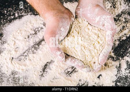 Hands holding white wheat flour - Stock Photo