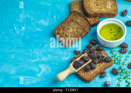 Traditional greek italian appetizer dried black olives with bread and olive oil served on over a blue concrete table surface background - Stock Photo