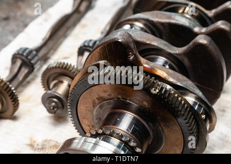 Close-up of a car crankshaft and shaft with gears and bearings removed for replacement on a workbench in a vehicle repair shop. Auto service industry. - Stock Photo
