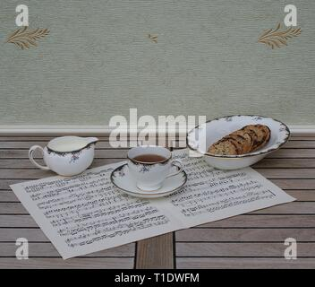 English teacup with saucer, cream jug and a cake bowl with cookies, fine bone china porcelain, on a sheet of music - Stock Photo