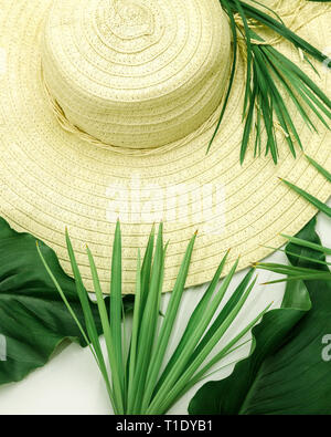 Yellow straw hat with green different leaves on white background. Top view and close-up. Summer holidays vacation concept. - Stock Photo