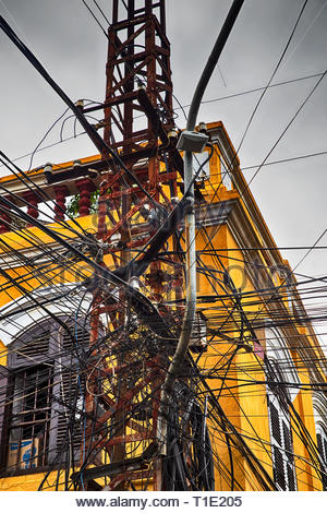 Image of an enormous amount of telephone and electric cables put together on a sinle post in a chaotic way, shot in Hoi An ancient city, Vietnam - Stock Photo