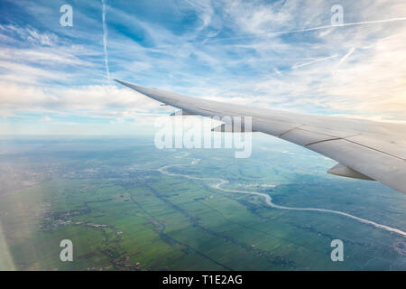 Jet airplane aeroplane plane trails contrails or Cirrus Aviaticus over Holland from the window of a Boeing 787 8 Dreamliner - Stock Photo