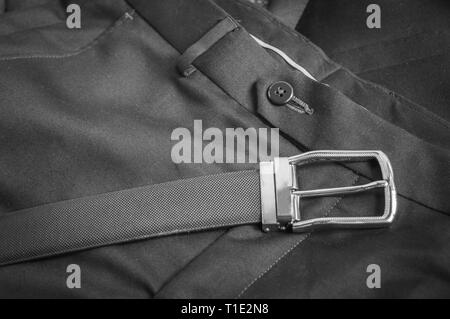 Black and white view of black leather belt kept on a formal pant trouser - Stock Photo
