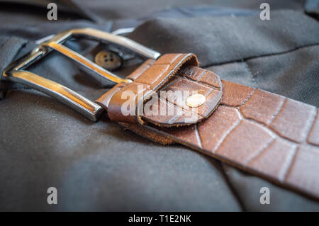 Buckle of a brown textured leather belt kept on a pant trouser - Stock Photo
