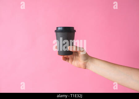 pink cardboard cup for coffee with a lid on a white