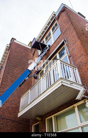 The Used blue Boom Lifts for repair and washing windows. Lift on the background of an old brick house with a window. - Stock Photo