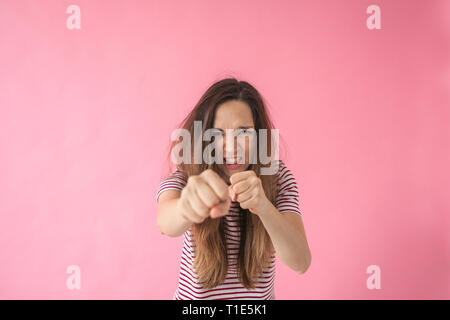 An angry or frustrated girl punches and shows aggression. Or she is training or boxing. - Stock Photo