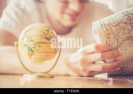 Miniature globe model and a young man looking in a map. Prepare for travelling. - Stock Photo