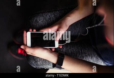 A midsection of young girl or woman with earphones and smartphone in a gym. - Stock Photo