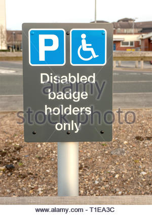 Street sign dictating that the parking space is reserved for holders of a UK disabled blue badge only. - Stock Photo