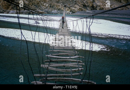 March 19, 2012 - Passu, Hunza District, Pakistan - FILE - Man crossing the Hussaini bridge in Passu, old suspension bridge, above the Hunza River in Hunza Valley (Credit Image: © Jordi Boixareu/ZUMA Wire) - Stock Photo