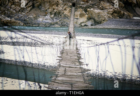 March 20, 2012 - Passu, Hunza District, Pakistan - FILE IMAGE taken on January 2000 - Man crossing the Hussaini bridge in Passu, old suspension bridge, above the Hunza River in Hunza Valley (Credit Image: © Jordi Boixareu/ZUMA Wire) - Stock Photo