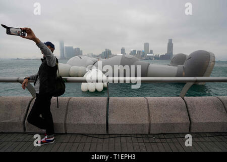 Hong Kong, China. 26th Mar, 2019. A visitor takes a photo of himself with the KAWS:HOLIDAY installation on display in Hong Kong's Victoria Harbor. The KAWS:Holiday enlarged structure by American artist Brian Donnelly, also known as KAWS, will be on display until March 31, 2019. Credit: Christopher Jue/ZUMA Wire/Alamy Live News - Stock Photo