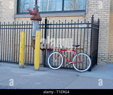 Red bicycle parked by a fence near two yellow posts protecting a large pipe with four spigots on the end. St Paul Minnesota MN USA - Stock Photo