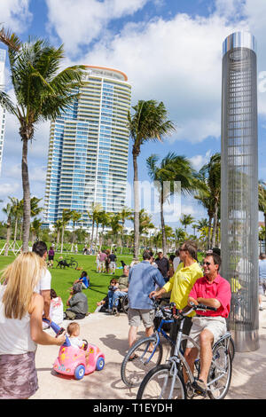 Miami Beach Florida South Pointe Park Grand Reopening event lawn crowd man woman child family cyclist bicycle baby turtle friend - Stock Photo