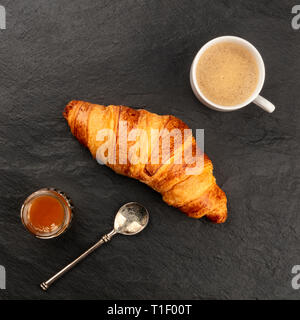 An overhead photo of a croissant with a cup of coffee and a jar of jam on a black background with copy space - Stock Photo