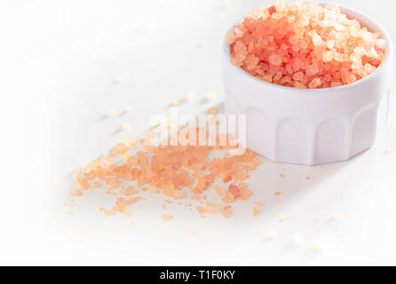 Big Crystals of pink Himalayan salt in ceramic jar. White background. - Stock Photo