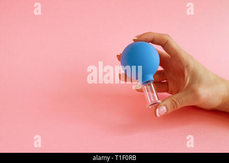female hand with French manicure holds blue cosmetic medical jar for vacuum facial massage on pink background. Glass, rubber, latex. - Stock Photo
