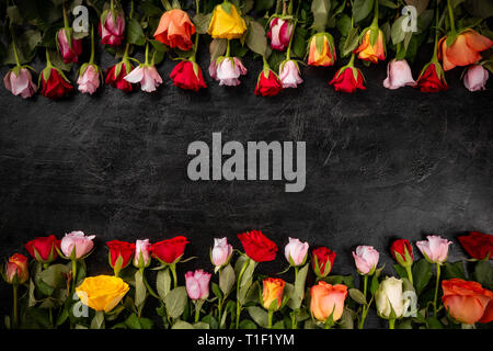 Flowers composition. Frame made of colourful rose flowers on black slate background - Stock Photo