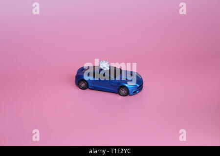 The blue sports car carries a crystal flower. The gift lies on the roof of the car. Pink background. Toy for children. There are no people. - Stock Photo