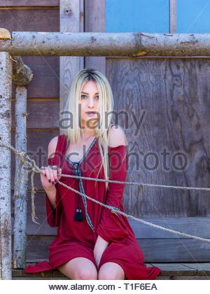 Shy pretty teen girl sitting on porch of wooden house serious looking at camera eyes-contact aka young woman - Stock Photo