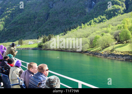 Flam, Norway - May 5 2014: Tourists are enjoying magnificent view of Fjord on board of ferry boat in Norway. - Stock Photo