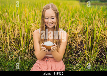 A woman is holding a cup of boiled rice in a wooden cup on the background of a ripe rice field - Stock Photo