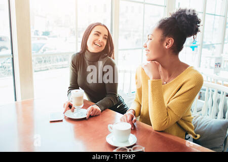 Two best friends are sitting in cafe and spending good time together. Girls are drinking some latte and enjoying their conversation. Close up. - Stock Photo