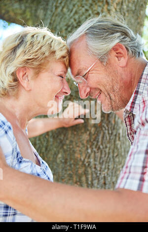 Amorous couple of seniors face forehead in the park while dating in summer - Stock Photo