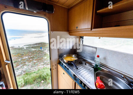 Cooking dinner or breakfast in camper RV with beach view. Preparing eggs with magnificant view of Nemiña beach Galicia Spain. Traveling with RV, motor - Stock Photo