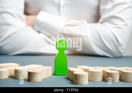 The green figure of a man stands between the lying people. Successful choice. The leader chooses the person in the the team. Talented worker. Promote. - Stock Photo