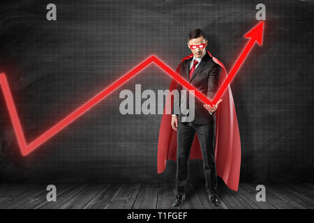 Businessman in black suit, red cape and red mask with glaring white eyes holding with one hand red graph arrow pointing up at black graph ruled wall. - Stock Photo