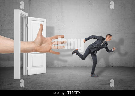 Businessman running away from a big hand out of an open door on grey wall background. - Stock Photo