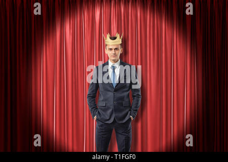 Young businessman wearing golden crown on red stage curtains background - Stock Photo
