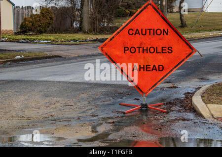 Orange triangular road sign on a small suburban street that says caution potholes ahead - Stock Photo