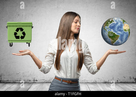 Young business woman holding earth globe and green trash can in her hands on grey wall background - Stock Photo