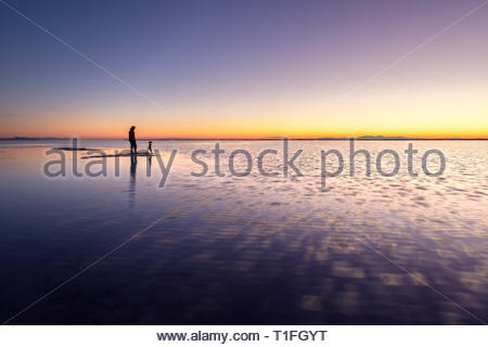 Photographer standing on the shallow water at dawn, Bonneville Salt Flats near Great Salt Lake, Utah - Stock Photo