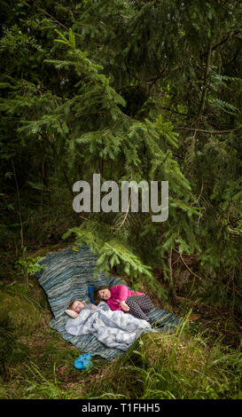 Tho girls resting at a camp under a pine tree in the forest. - Stock Photo