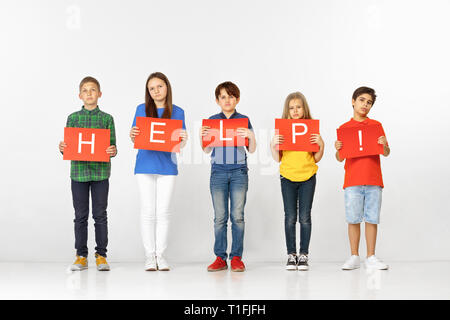 Help warms the heart. Group of sad serious children or teenagers with red banners making word isolated on studio background. Education, advertising and social rights concept. Family problems concepts. - Stock Photo