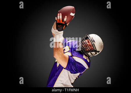 American football sportsman player on black background. Sport concept. - Stock Photo