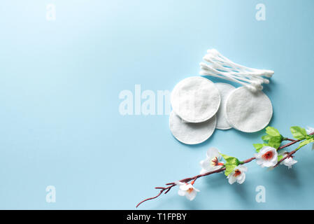 Cotton swabs and cotton pads with flowers on a blue background.top view.disk for beauty face hygiene . skin, body care concept.selective focus. place  - Stock Photo