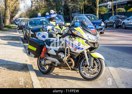 French motorcycle police officers have parked their motorbikes on the side of the road and dismounted to watch the traffic and the drivers behavior. - Stock Photo