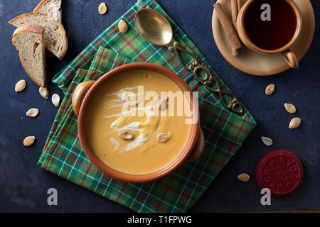 Pumpkin soup, red fruit tea, geen dish cloth andsome bread all served to be ready-to-eat. Flatlay, directly above, top down view - Stock Photo