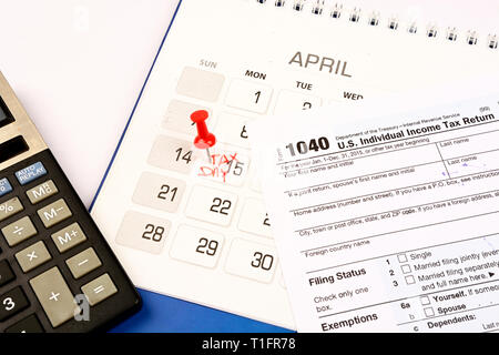 Red pushpin in calendar on 15th April for US tax day - Stock Photo