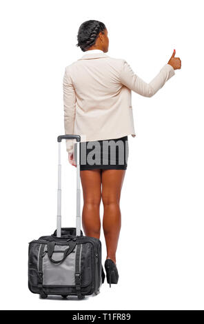 Back view of stylishly dressed business black woman with suitcase shows thumb up. Standing young African American girl. Rear view people collection.   - Stock Photo