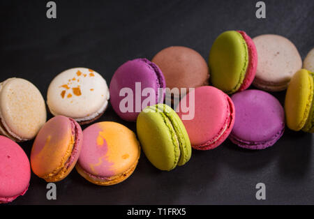 Assorted colorful macaroons on a dark background - Stock Photo