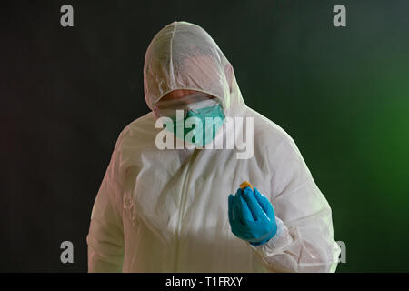 Man in chemical suit inspecting possible toxic materials - Stock Photo