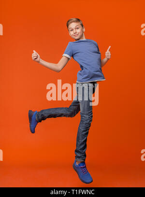 School boy jumping and making thumbs up - Stock Photo